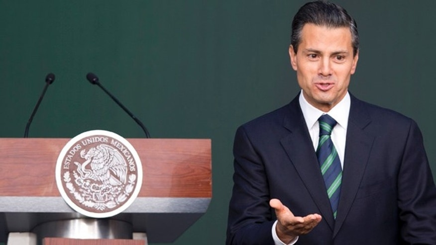 November 27, 2014: Mexico's President Enrique Pena Nieto gestures after addressing the audience during a ceremony at the National Palace in Mexico City. (AP Photo/Eduardo Verdugo)