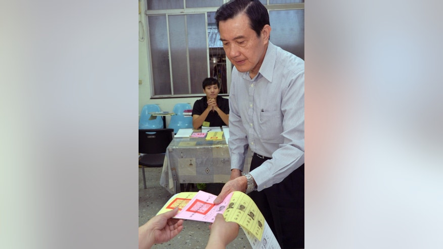Taiwan's President Ma Ying-jeou receives his ballots to cast his votes in the local elections including Taipei mayor in Taipei, Taiwan, Saturday, Nov. 29, 2014. Taiwan's relations with historic foe China are playing a key role in local elections on the self-ruled island Saturday as the ruling Nationalist Party meets increased resistance to forging stronger ties with Beijing. (AP Photo/Central News Agency, Pool)