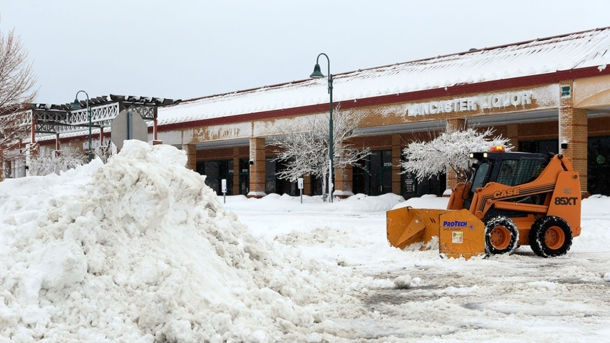 KANSAS CITY, MO - FEBRUARY 26:  A snowplow helps clear a supermarket parking lot after the area is hit by a snowstorm on February 26, 2013 in Kansas City, Missouri. This is the second major snowstorm the midwest has seen this week dropping a half-foot or more of snow across Missouri and Kansas and cutting power to thousands...  (Photo by Jamie Squire/Getty Images)