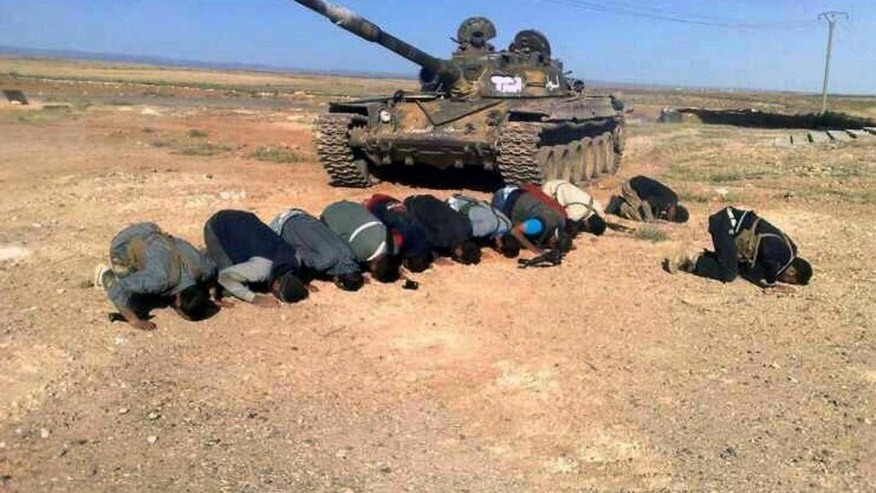 FILE - In this April 30, 2014, file image provided by the Syrian Revolution Against Bashar Assad, which has been authenticated based on its contents and other AP reporting, Syrian rebels pray in front of their tank at al Mutayia village in the southern province of Daraa, Syria. Syrian rebels backed by the United States are making their biggest gains yet south of the capital Damascus, capturing a string of towns from government forces and aiming to carve out a swath of territory leading to the doorstep of President Bashar Assad's seat of power. (AP Photo/the Syrian Revolution Against Bashar Assad, File)
