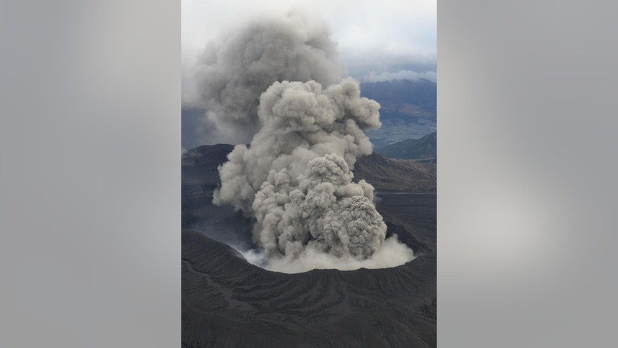 In this Nov. 26, 2014 photo, volcanic smoke billows from Mount Aso, Kumamoto prefecture, on the southern Japanese main island of Kyushu. The volcano is blasting out chunks of magma in the first such eruption in 22 years, causing flight cancellations and prompting warnings to stay away from its crater. The Japan Meteorological Agency said Friday, Nov. 28 that Mount Aso had spewed out lava debris and smoke, shooting plumes of ash a kilometer (3,280 feet) into the sky. The observatory does not expect the eruption to increase in scale. (AP Photo/Kyodo News) JAPAN OUT, MANDATORY CREDIT