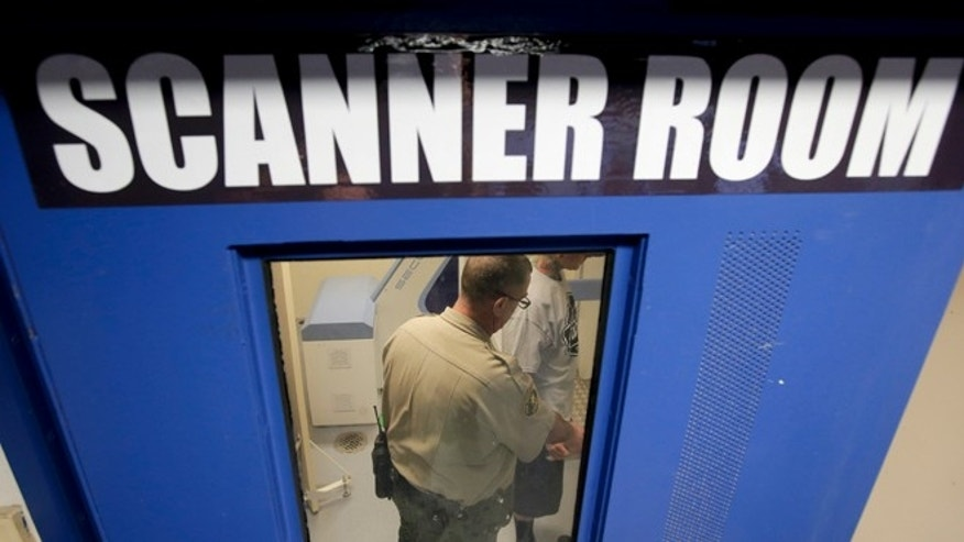 In this Nov. 20, 2014 photo, Deputy Robert J. Rudisill takes a prisoner though a body scan after being taken into custody at San Diego County sheriffs Vista Detention Center in Vista, Calif. The facility receives male and female inmates from all the cities in northern San Diego County. (AP Photo/Chris Carlson)