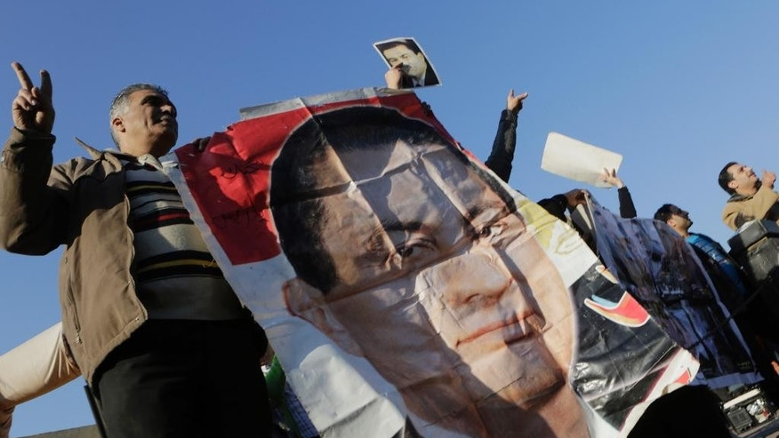 Supporters of former Egyptian President Hosni Mubarak wave by his poster as he was taken by a helicopter ambulance from Maadi Military Hospital to a court in Cairo, Egypt, Saturday, Nov. 29, 2014. The verdict is expected Saturday on charges connected to the killing of more than 900 protesters during the year's uprising against his rule. (AP Photo/Amr Nabil)