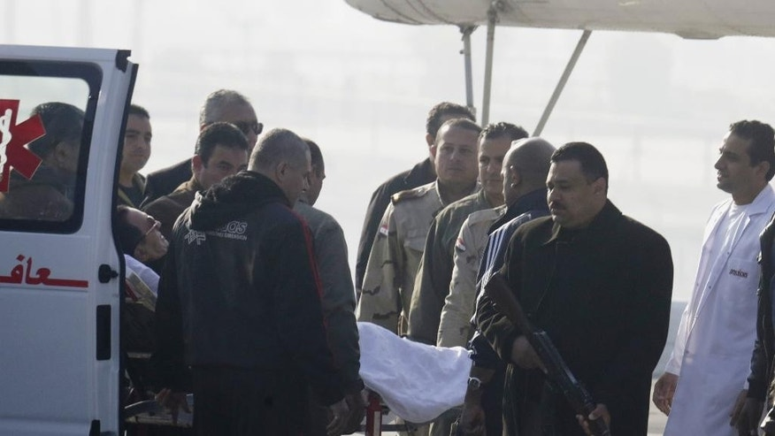 Former Egyptian President Hosni Mubarak, 86, is escorted by medical and security personnel into an ambulance on the way to a helicopter ambulance flying from Maadi Military Hospital to a court in Cairo, Egypt, Saturday, Nov. 29, 2014. The verdict is expected Saturday on charges connected to the killing of more than 900 protesters during the year's uprising against his rule. (AP Photo/Amr Nabil)