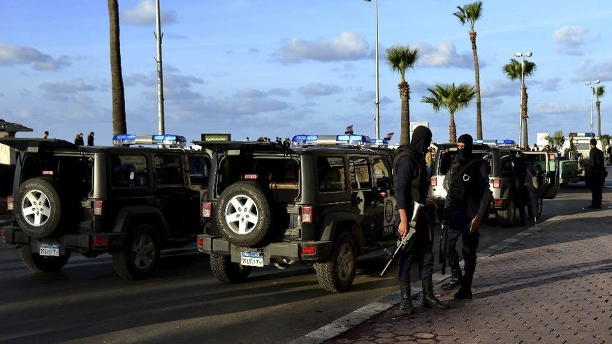 Egyptian security forces stand by their vehicles as they were deployed to disperse anti-government protesters in Alexandria, Egypt, Friday, Nov. 28, 2014. Egyptian security forces quickly put down scattered protests Friday as an attempt by Islamists to hold the first major anti-government rallies in months fizzled, with at least two protesters and three army officers killed in Cairo and a navy officer killed in Alexandria. (AP Photo/Heba Khamis)