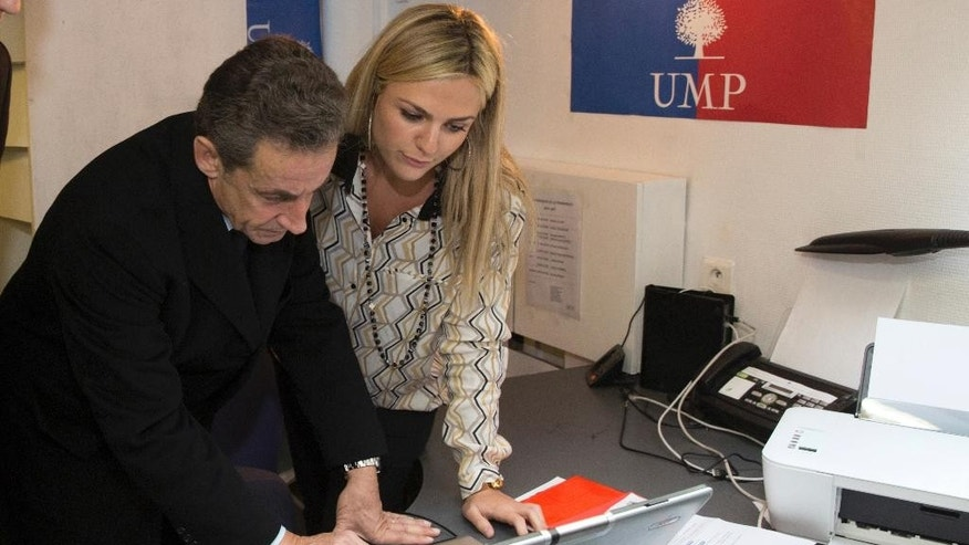 Former French President Nicolas Sarkozy votes at a UMP party permanence for the leadership of France's main opposition party, the UMP (Union for a Popular Movement), in Paris, Saturday, Nov. 29, 2014. France's main opposition party, the UMP, is holding elections Friday and Saturday for a new leader between France's former President Nicolas Sarkozy, Bruno Le Maire and Herve Mariton. (AP Photo/Philippe Wojazer, Pool)