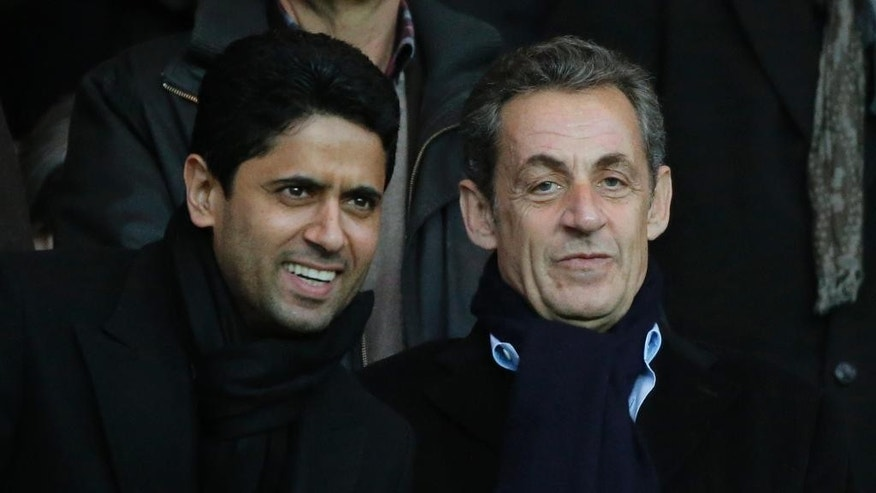 Former French President Nicolas Sarkozy and Paris Saint Germain's President Nasser al-Khelaifi attend the League One soccer match between Paris Saint Germain and Nice, at Parc des Princes stadium, Saturday, Nov. 29, 2014. France's main opposition party, the UMP, is holding elections Friday and Saturday for a new leader between France's former President Nicolas Sarkozy, Bruno Le Maire and Herve Mariton. (AP Photo/Francois Mori)