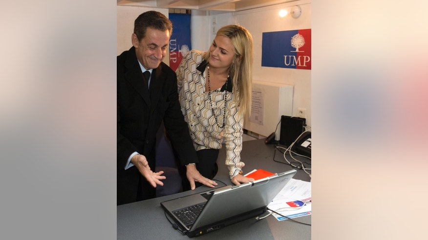 French former President Nicolas Sarkozy votes at a UMP party permanence for the leadership of France's main opposition party, the UMP (Union for a Popular Movement), in Paris, Saturday, Nov. 29, 2014. France's main opposition party, the UMP, is holding elections Friday and Saturday for a new leader between France's former President Nicolas Sarkozy, Bruno Le Maire and Herve Mariton. (AP Photo/Philippe Wojazer, pool)