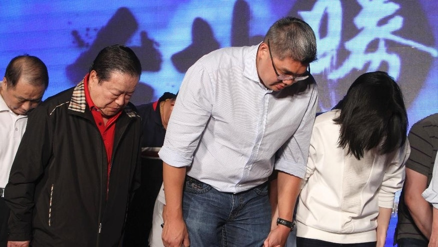 Taiwan's ruling Nationalist Party mayoral candidate Sean Lien, center, bows as he concedes lost in the Taipei mayoral election at his party's headquarters, Saturday, Nov. 29, 2014, in Taipei, Taiwan. In preliminary results, Taiwan's ruling Nationalist Party lost eight city and county elections Saturday, a stronger than expected jolt for the president who has staked his reputation on stronger ties with old foe Beijing despite increasing contempt at home. (AP Photo/Chiang Ying-ying)