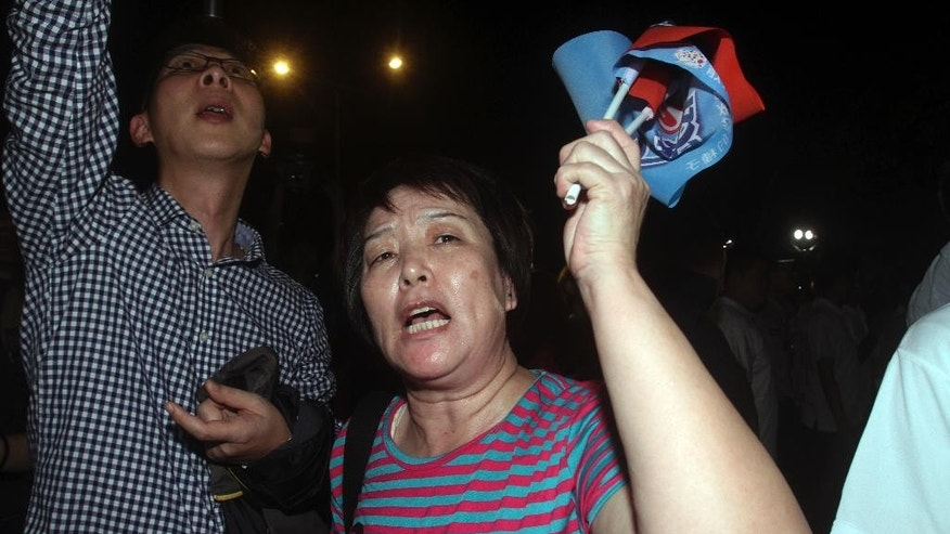 Supporters of Taiwan's ruling Nationalist Party react after a preliminary vote count shows their mayoral candidate Sean Lien lost, Saturday, Nov. 29, 2014, in Taipei, Taiwan. With more than 80 percent of precincts reporting Saturday, the Nationalist Party had lost eight city and county elections, including in longtime strongholds Taipei and Taichung. (AP Photo/Chiang Ying-ying)