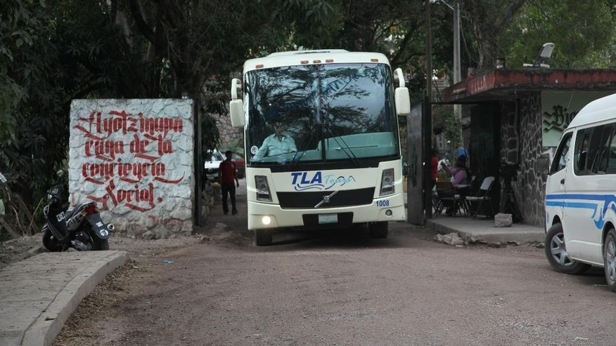 In this Nov. 10, 2014 photo, a bus leaves the Raul Isidro Burgos Rural Normal School of Ayotzinapa, where the 43 missing students attended, in the town of Tixtla de Guerrero, Mexico. While world attention has turned to the students of the rural teachers college in southern Mexico, almost no one has noticed the 30 or so bus drivers who say they are being forced to live as captives in order to act as chauffeurs for the activists who commandeered their vehicles. The men, some who've been at the school more than a month, say they cannot abandon the field because the bus companies hold them financially responsible for the vehicles worth tens of thousands of dollars. And with authorities unwilling to inflame tensions over the disappearance and presumed massacre of 43 students from the school, no one is coming to their rescue. (AP Photo/Marco Ugarte)