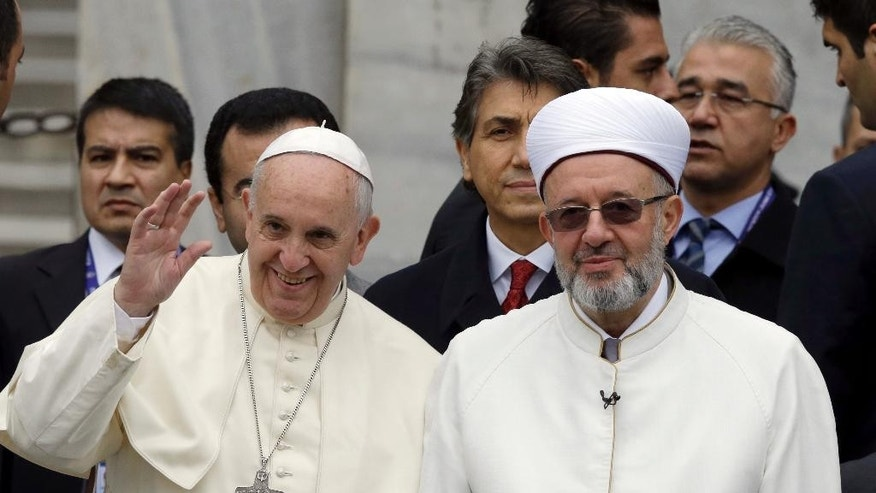 "Pope Francis waves to journalists as he stands by Istanbul Mufti Rahmi Yaran upon their arrival to the Blue Mosque in Istanbul, Turkey, Saturday, Nov. 29, 2014. Pope Francis visits two of Turkey's most iconic sites and shifts gears toward more religious affairs as he arrives in Istanbul for the second leg of his three-day visit to the Muslim nation. The Vatican says Francis will tour Istanbul's Sultan Ahmet mosque on Saturday and pause for a moment of ""reflection."" (AP Photo/Thanassis Stavrakis)"