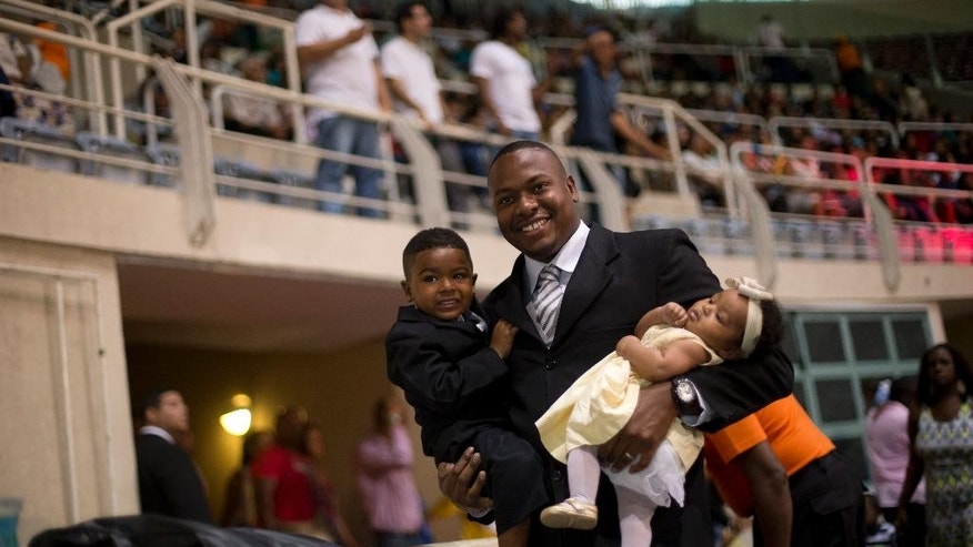 """A fiance arrives for his wedding as he carries his kids during a massive wedding ceremony at the Maracanazinho gymnasium, in Rio de Janeiro, Brazil, Sunday, Nov. 30, 2014. About 2000 couples married during a massive wedding ceremony called the """"Day of Yes"""", that was the biggest ever in Rio de Janeiro. (AP Photo/Silvia Izquierdo)"""