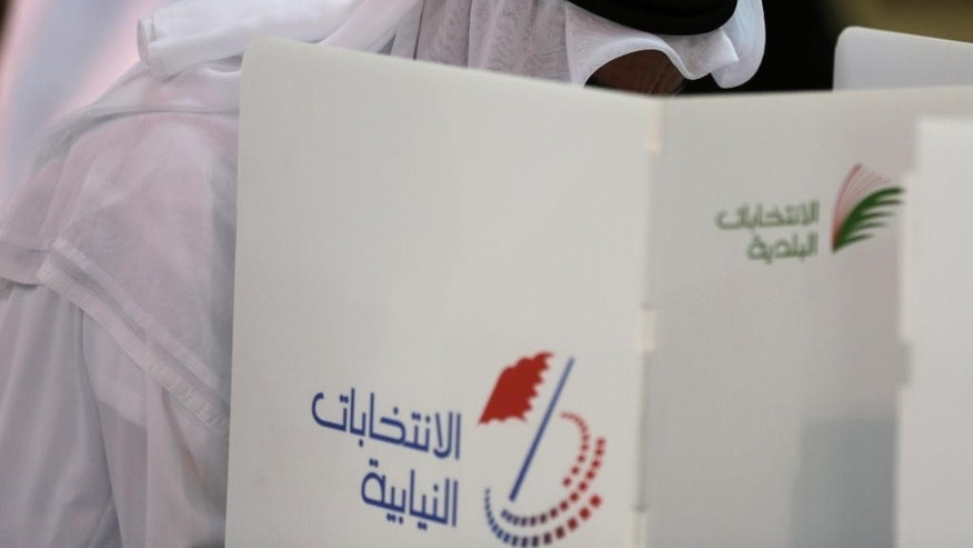 A Bahraini man votes in Manama, Bahrain, Saturday, Nov. 29, 2014. Bahraini voters are returning to the polls Saturday for a runoff election being boycotted by the opposition for the country's first new parliament since widespread Arab Spring-inspired protests nearly four years ago. (AP Photo/Hasan Jamali)