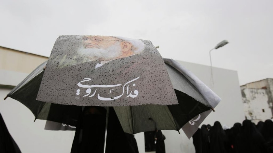 "A Bahraini woman walks with pictures of the nation's top Shiite Muslim cleric, Sheik Isa Qassim, on her umbrella in a march of support held in the rain after midday prayers in Diraz, Bahrain, Friday, Nov. 28, 2014. Many Bahraini Shiite Muslims responded to a call to head to Diraz for midday prayers to show support for Qassim, whose home was raided by police earlier this week. Arabic writing reads: ""I sacrifice my soul for you."" (AP Photo/Hasan Jamali)"