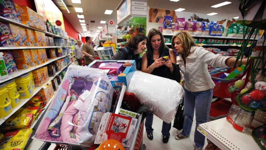 FILE - In this Nov. 28, 2014 file photo, Target shoppers Kelly Foley, left, Debbie Winslow, center, and Ann Rich use a smartphone to look at a competitor's prices while shopping  shortly after midnight on Black Friday, in South Portland, Maine. The Black Friday shopping weekend may be losing its mojo. A survey of shoppers released Sunday, Nov. 30, 2014, by the National Retail Federation shows how early discounting, more online shopping and an improving economy have fewer people shopping on the weekend that kicks off the holiday shopping season. (AP Photo/Robert F. Bukaty, File)
