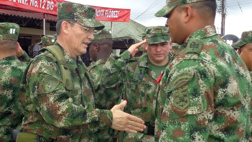 Colombian Army Gen. Ruben Dario Alzate, left, reaching to shake hands with a soldier in Bogota, Colombia.