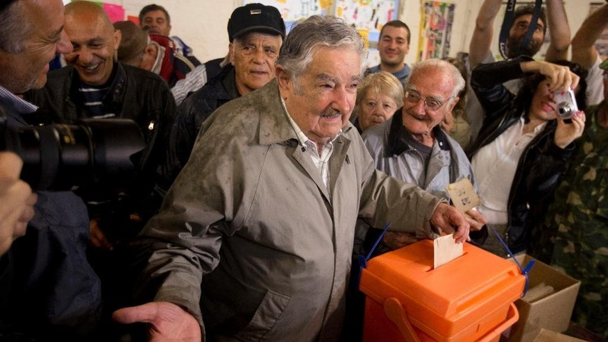 Uruguay's president, Jose Mujica, casts his vote during the presidential runoff election, Sunday, Nov. 30, 2014, in Montevideo, Uruguay. Broad Front coalition candidate and former president Tabare Vazquez is favored to win the runoff on the back of a strong economy. (AP Photo/Natacha Pisarenko)