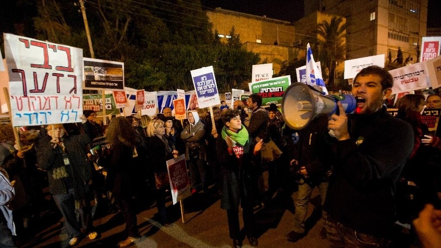 "Left wing Israelis hold signs and chant slogans during a demonstration to protest a controversial proposed law that would define Israel as ""the Jewish state,"" in Jerusalem, Saturday, Nov. 29, 2014. Hebrew on sign on the left reads: ""Bibi racist, not democratic, not Jewish.""  referring to Israeli Prime Minister Benjamin Netanyahu. (AP Photo/Sebastian Scheiner)"