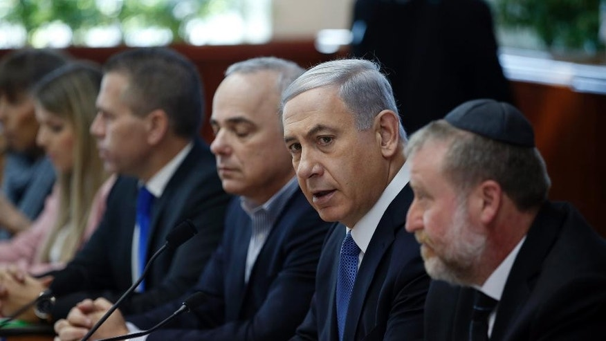 """Israel's Prime Minister Benjamin Netanyahu, second left, chairs the weekly cabinet meeting in Jerusalem, Sunday, Nov. 30, 2014. Israel's prime minister said Sunday that the public expects the government to """"return to normal conduct"""" and hinted at the possibility of early elections if his coalition does not overcome a crisis linked to a contentious nationality bill that would enshrine Israel's status as a Jewish state. The proposal would also make Jewish law a source of legislative inspiration and delist Arabic as an official language. (AP Photo/Ronen Zvulun, Pool)"""