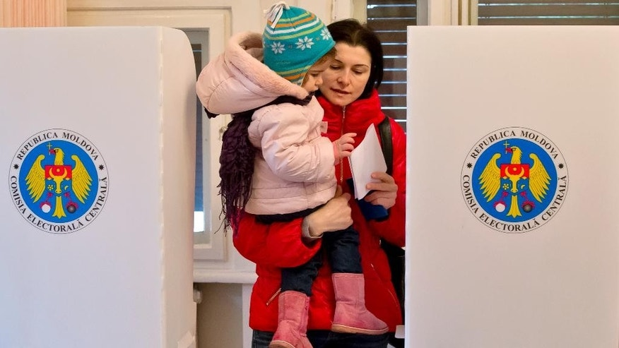 A baby reaches for a Moldovan woman's ballot as she votes at a station inside Moldova's embassy in Bucharest, Romania, Sunday, Nov. 30, 2014. Moldovans are voting in elections to choose between parties that want to move closer to Europe and those that want to move back into Russia's orbit. Sunday's parliamentary election takes on wider significance with the unrest in neighboring Ukraine. Moldova, like Ukraine, has a pro-Russia separatist region in its east. (AP Photo/Vadim Ghirda)