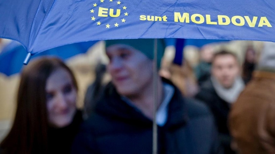 "Moldovan students hold an umbrella that uses the European Union symbol to form the sentence ""I am Moldova""  after arriving in the Romanian capital to vote, at the main railway station, Gara de Nord, in Bucharest, Romania, Sunday, Nov. 30, 2014. Moldovans vote in elections where they are choosing between parties that want to move closer to Europe and those that want to move back into Russia's orbit.Sunday's parliamentary election takes on wider significance with the unrest in neighboring Ukraine. Moldova, like Ukraine, has a pro-Russia separatist region in its east.(AP Photo/Vadim Ghirda)"