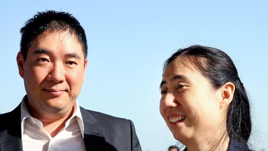 American couple Grace, right, and Matthew Huang arrive at the Hamad International Airport in Doha, Qatar, Sunday, Nov. 30, 2014. A Qatari appeals court on Sunday overturned a ruling against an American couple over the death of their adopted daughter and said they are free to leave, ending a closely watched legal saga that may have stemmed from cultural misunderstandings in the conservative Gulf nation. (AP Photo/Osama Faisal)