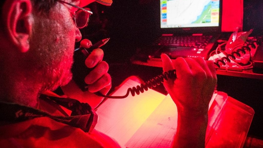 In this image provided by Team Alvimedica/Volvo Ocean Race, navigator Will Oxley communicates with Team Vestas Wind over VHF during Leg 2 of the Volvo Ocean Race between Cape Town, South Africa, and Abu Dhabi, Saturday, Nov. 29, 2014. Nine crewmen from Team Vestas Wind were rescued after abandoning their 65-foot sloop that ran aground on a reef off Mauritius in the Indian Ocean during the race. The sailors will stay on the remote Ile du Sud, where there is a house and some facilities, race officials said late Saturday night. There were no injuries. Danish-backed Team Vestas Wind was making plans with race officials on how to get the crew off the island and salvage the sloop. (AP Photo/Team Alvimedica/Volvo Ocean Race, Amory Ross)