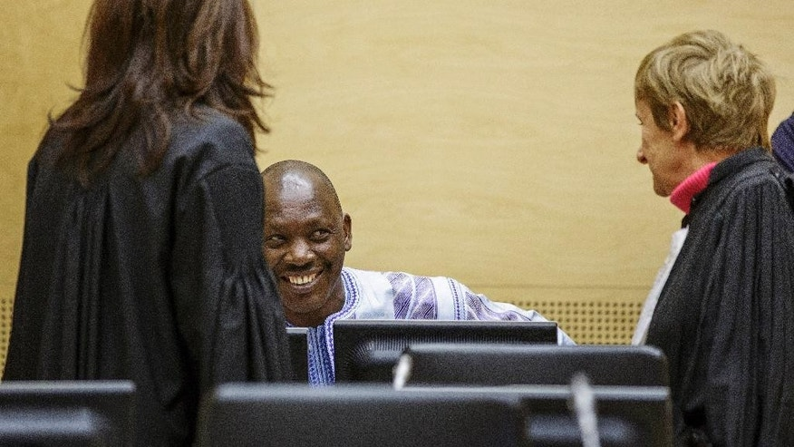 Congolese militia leader Thomas Lubanga, second left, who was convicted in March 2012 of recruiting and using child soldiers in 2002 and 2003, talks to his defence team as he waits for the judges to rule on his appeal at the International Criminal Court in The Hague Monday Dec. 1, 2014. Appeals judges at the International Criminal Court have upheld the conviction of a Lubanga who had been sentenced to 14 years for recruiting and using child soldiers, bringing to an end the court's first trial which was hailed as a landmark in international justice and a deterrent that would resonate around the world. (AP Photo/Michael Kooren, Pool)