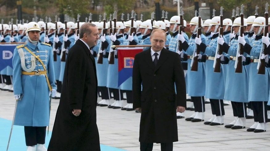 Russian President Vladimir Putin, right, and his Turkish counterpart  Recep Tayyip Erdogan inspect military honour guard during a welcome ceremony at the new Presidential Palace in Ankara, Turkey, Monday, Dec. 1, 2014. Putin arrived in Turkey for a one-day visit and he will meet with Erdogan at his huge new palace on once-protected farm land and forest in Ankara, becoming the second foreign dignitary after the Pope Francis to be hosted at the lavish, 1000-room complex.(AP Photo/Burhan Ozbilici)