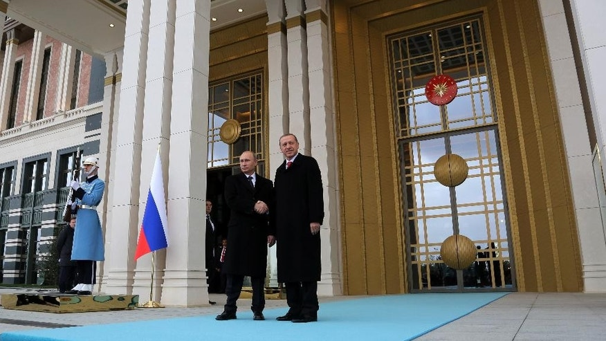 Russian President Vladimir Putin, left, and his Turkish counterpart  Recep Tayyip Erdogan shake hands after a welcome ceremony at the new Presidential Palace in Ankara, Turkey, Monday, Dec. 1, 2014. Putin arrived in Turkey for a one-day visit and he will meet with Erdogan at his huge new palace on once-protected farm land and forest in Ankara, becoming the second foreign dignitary after the Pope Francis to be hosted at the lavish, 1000-room complex.(AP Photo/Burhan Ozbilici)
