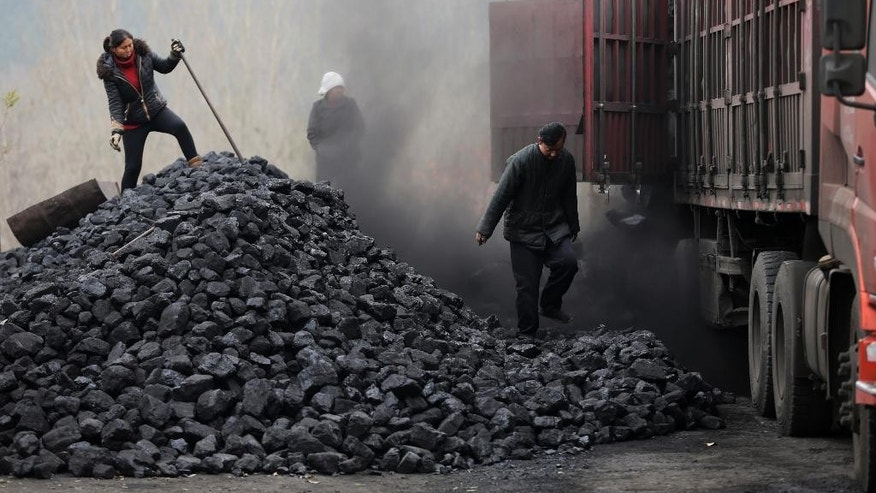 Nov. 27, 2014: Workers load coal from a truck at a process station for sale in Tangxian in China's Hebei province.