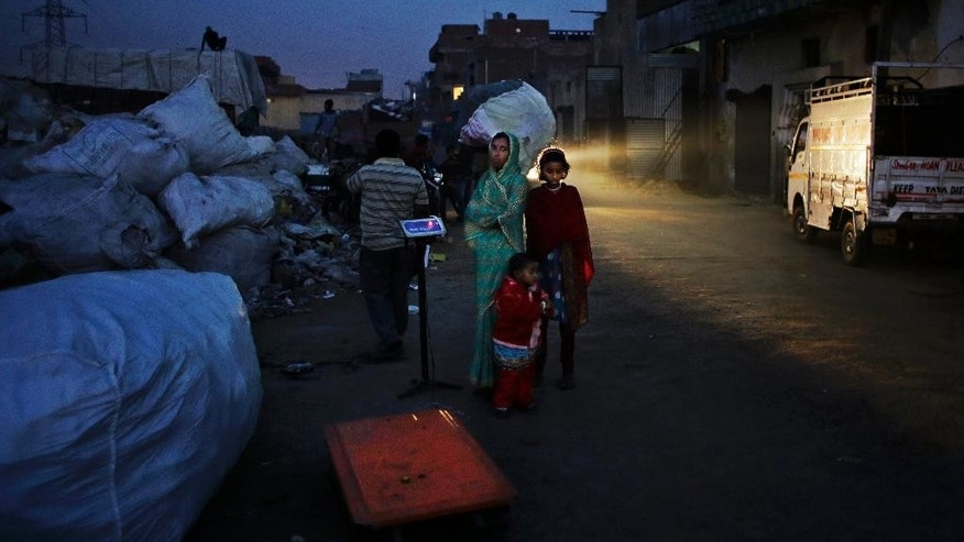 In this Nov. 13, 2014 photo, Marjina and her 12-year old daughter Murshida wait for a trash dealer to weigh their segregated trash on the outskirts of New Delhi, India. Marjina arrived in New Delhi with her two children, hoping to find a better life after her husband abandoned them without so much as a goodbye. The family spends their day at a landfill picking through other people's garbage to find salvageable bits to resell or recycle. The family earned just $26 per month. (AP Photo/Altaf Qadri)