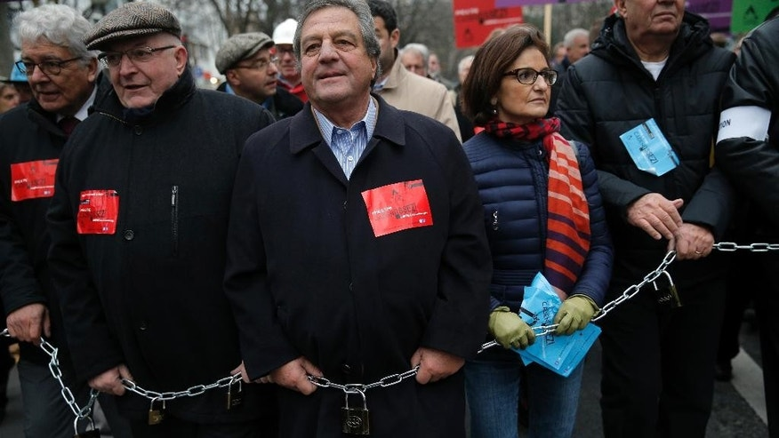 Small and medium-sized enterprise owners hold padlocks as they demonstrate in Paris, France, Monday, Dec. 1, 2014. Several thousand French business owners, particularly from small companies, demonstrated to plead with the government to simplify regulations and make it easier and cheaper to hire. (AP Photo/Christophe Ena)