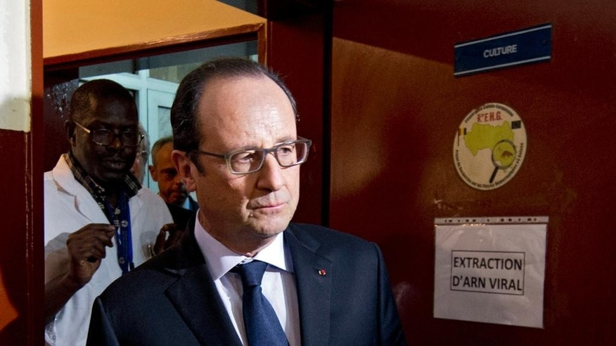 French President Francois Hollande visits the French Pasteur institute laboratory at Donka hospital in Conakry, Guinea, Friday Nov. 28, 2014. Hollande is visiting the Ebola stricken country during a seven-hour stop on his way to Dakar, Senegal. (AP Photo/Alain Jocard, Pool)