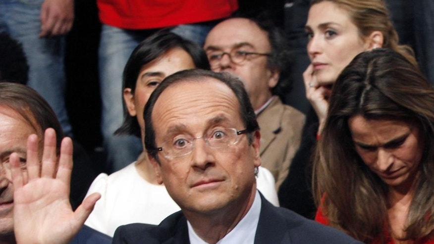 """FILE - This Oct. 22, 2011 file photo shows then French Socialist Party candidate for the 2012 presidential elections Francois Hollande, at a nomination ceremony, in Paris, with French actress Julie Gayet in background, top right. The French presidency confirmed Monday, Dec.1 2014 the transfer of five staff members previously assigned to Hollande's """"private service"""", after reports by French media that photos of Hollande with Gayet inside the Elysee palace were taken from within the presidential private apartments. (AP Photo/Thibault Camus, File)"""