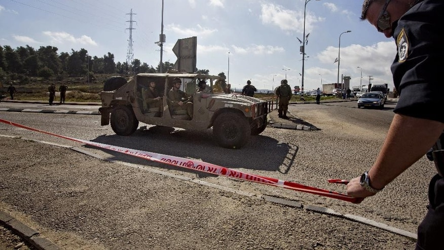 Dec. 1, 2014 - Israeli soldiers and police officers stand at the scene of a stabbing attack at the West Bank Gush Etzion junction near Jerusalem. A Palestinian woman stabbed and slightly wounded an Israeli civilian in the West Bank, the Israeli military said. Eyewitnesses said the attacker involved was shot by security forces in the area and taken for medical treatment.