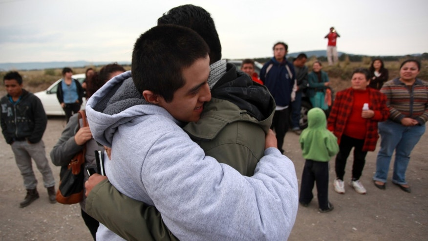 Juan Daniel Lopez Avila, left, is embraced by an unidentified relative after he was released from a maximum security federal prison in the town of Villa Aldama, in the Gulf state of Veracruz, Mexico, Saturday Nov. 29, 2014. Avila and ten other activists were arrested and charged with mutiny, attempted murder and other federal charges by Mexico's Attorney General's Office after their participation in the massive Mexico City protests on Nov. 20th that demanded justice over the case of the 43 missing students. According to one of the lawyers, the activists were released for lack of evidence. (AP Photo/Felix Marquez)