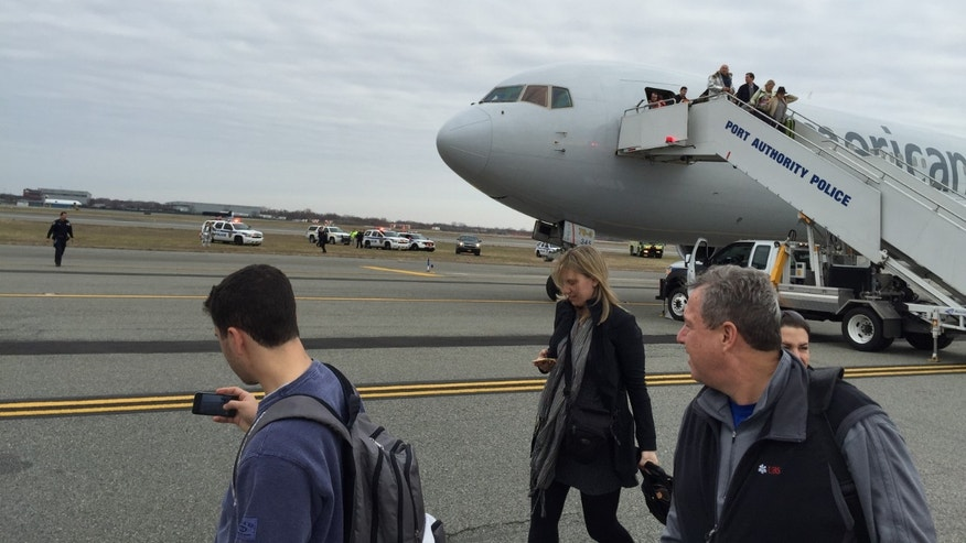 In a Sunday, Nov. 30, 2014 photo provided by Jacob Rosenberg, passengers deplane from American Airlines flight 67 after it landed at John F. Kennedy International Airport in New York, Sunday. Authorities at John F. Kennedy International Airport are investigating a bomb threat made to American Airlines Flight 67 from Barcelona that landed safely in New York City. (AP Photo/Jacob Rosenberg) NO SALES
