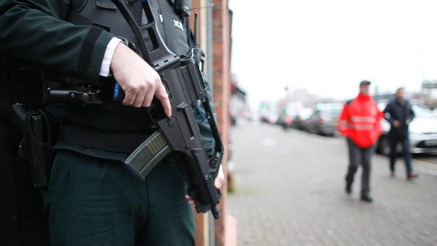 A police officer stands on security patrol in South Belfast, Northern Ireland, Monday, Dec. 1, 2014.  Northern Ireland's police say they are increasing security operations in the run-up to Christmas to combat an increasing threat from Irish Republican Army bombers. Assistant Chief Constable Will Kerr said Monday that police would mount road checkpoints on key Belfast roads in hopes of deterring the kinds of attacks that rattled Belfast before Christmas last year.  (AP Photo/Peter Morrison)