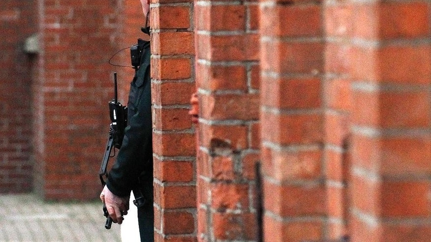 A police officer stands on security patrol in the Ormeau Avenue, in South Belfast, Northern Ireland, Monday, Dec. 1, 2014.  Northern Ireland's police say they are increasing security operations in the run-up to Christmas to combat an increasing threat from Irish Republican Army bombers. Assistant Chief Constable Will Kerr said Monday that police would mount road checkpoints on key Belfast roads in hopes of deterring the kinds of attacks that rattled Belfast before Christmas last year.  (AP Photo/Peter Morrison)