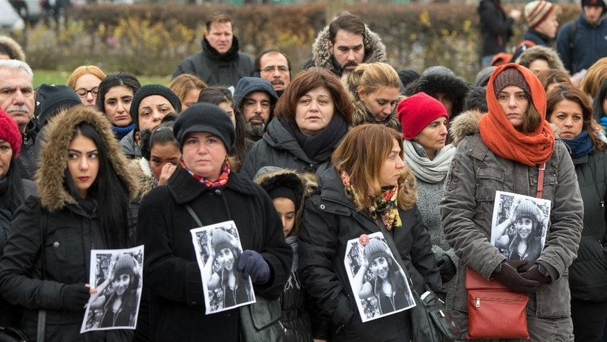 Demonstrators take part in a rally while showing photographs  to remember student Tugce in Berlin, Germany, Sunday Nov. 30,  2014. They  commemorate 23-year old Tugce A. who was beaten up two weeks ago in front of a fast food branch when she tried to help two other girls in Offenbach, near Frankfurt Germany. She was declared brain dead and the medical equipment was switched off  Friday which was  also her 23.  birthday. (AP Photo/dpa,Maurizio Gambarini)