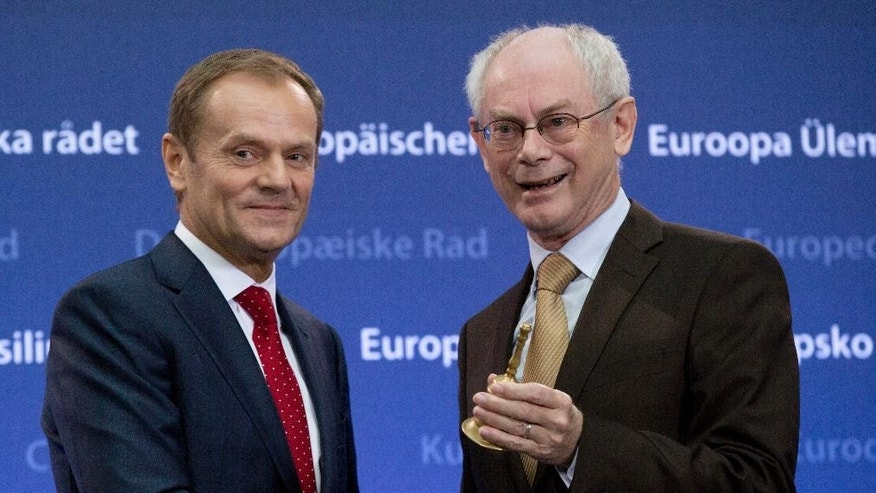 Outgoing European Council President Herman Van Rompuy, right, prepares to give incoming European Council President Donald Tusk a bell during a handover ceremony for the European Council Presidency at the EU Council building in Brussels on Monday, Dec. 1, 2014. Poland's former prime minister Donald Tusk is pushing the EU's center of political gravity eastward by taking over the EU Presidency from Belgium's Herman Van Rompuy. Monday's transition ceremony highlighted the increasing power of Poland within the 28-nation EU and further shift from a west European economic association to a strong political body uniting some 500 million people from Britain to the borders of Russia in the east. (AP Photo/Virginia Mayo)