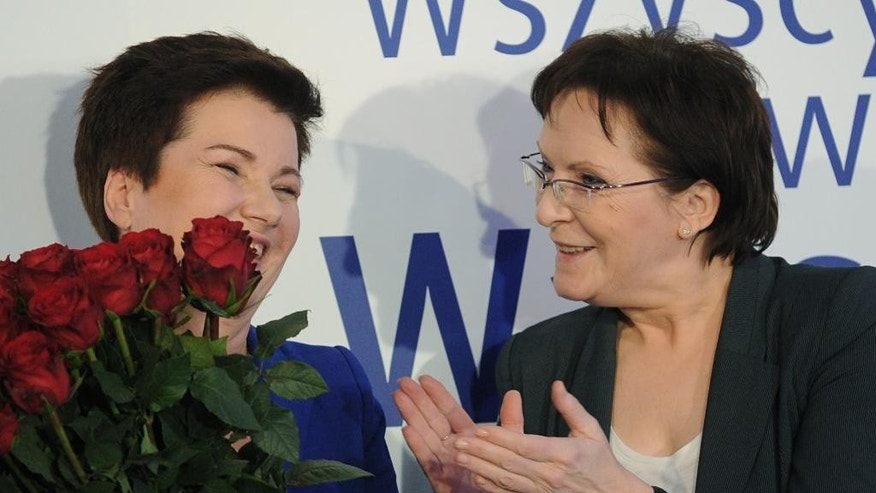 Polish Prime Minister Ewa Kopacz, right, congratulates Mayor of Warsaw Hanna Gronkiewicz-Waltz as first exit polls are announced after the end of local elections runoff, in Warsaw, Poland, Sunday, Nov. 30, 2014. The elections are considered a test of strength for new Prime Minister Ewa Kopacz and the ruling Civic Platform party ahead of presidential and parliamentary elections next year. Problems with the computerized vote count of the first round spurred opposition leader Jaroslaw Kaczynski to question the validity of the results. (AP Photo/Alik Keplicz)