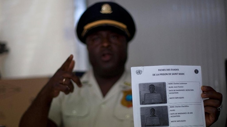 Saint Marc police Commissioner Berson Soljour holds a list showing several of the thirty-four prisoners who escaped the prison of Saint-Marc, Haiti, Monday, Dec. 1, 2014. Commissioner Soljour said four of the men had been recaptured, but the rest remained at large. (AP Photo/Dieu Nalio Chery)