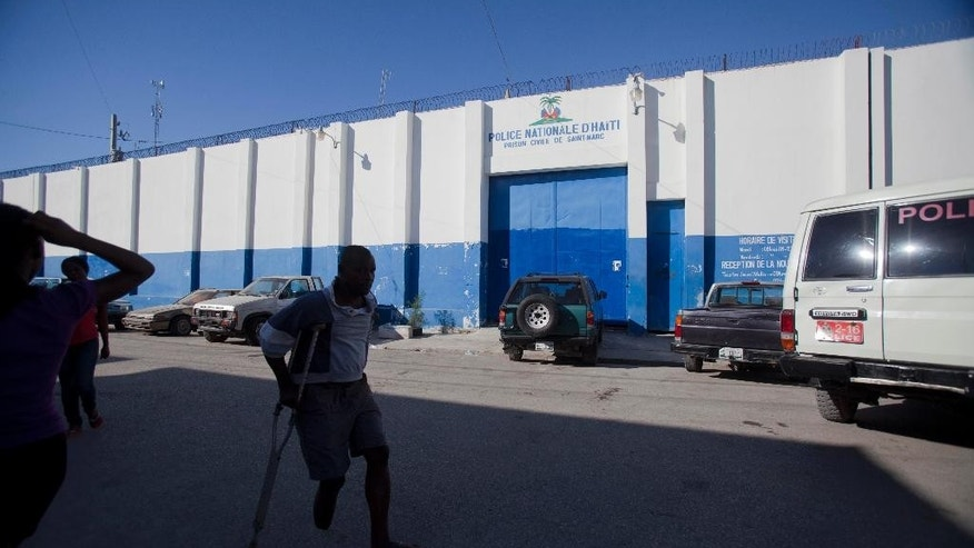 Residents walk past the front of the Saint-Marc prison, in Saint-Marc, Haiti, Monday, Dec. 1, 2014. Nearly three dozen prisoners awaiting trial in a crowded jail in a provincial city north of the Haitian escaped by sawing through steel bars, authorities said Monday. (AP Photo/Dieu Nalio Chery)