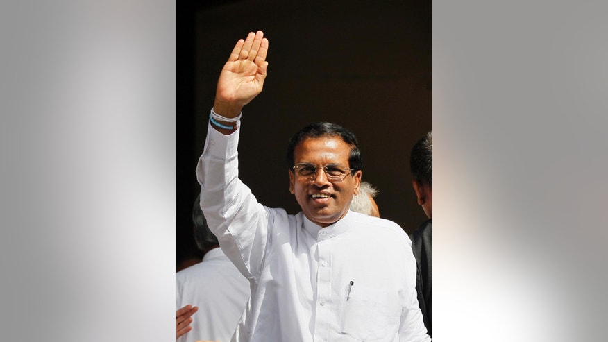 Former Sri Lankan Health Minister and presidential candidate of the common opposition Maithripala Sirisena waves to his supporters during an event in Colombo, Sri Lanka, Monday, Dec. 1, 2014. Sirisena on Monday signed an agreement with opposition parties, trade unions and professional groups to scrap the country's powerful presidential system and carry out other democratic reforms if he beats incumbent Mahinda Rajapaksa and wins January's presidential election. (AP Photo/Eranga Jayawardena)