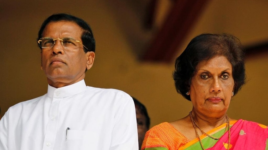 Former Sri Lankan Health Minister and presidential candidate of the common opposition Maithripala Sirisena, left, and former Sri Lankan President Chandrika Kumaratunge attend an event in Colombo, Sri Lanka, Monday, Dec. 1, 2014. Sirisena on Monday signed an agreement with opposition parties, trade unions and professional groups to scrap the country's powerful presidential system and carry out other democratic reforms if he beats incumbent Mahinda Rajapaksa and wins January's presidential election. (AP Photo/Eranga Jayawardena)