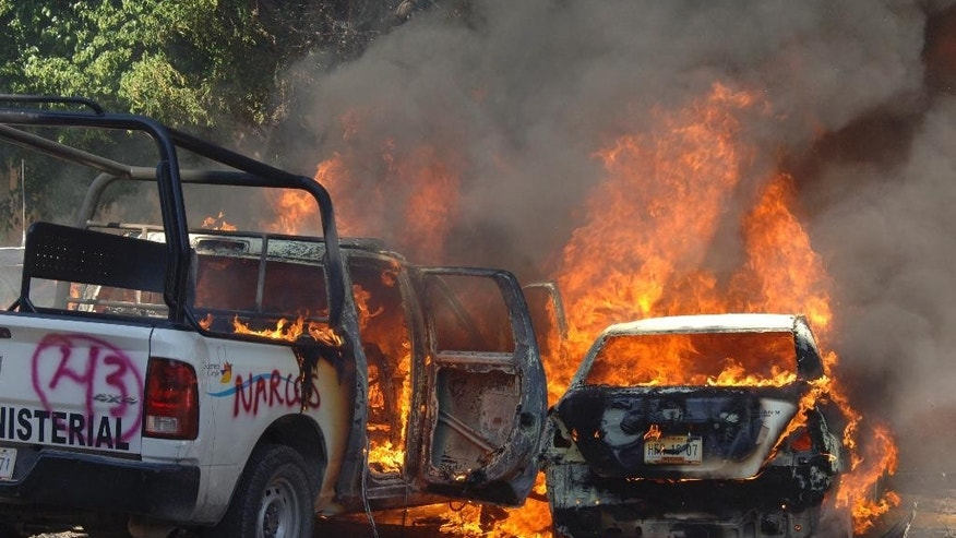 Police vehicles burn after teachers marching to demand justice for the 43 missing students, attacked the State Attorney General's offices in the state capital city of Chilpancingo, Mexico, Monday Dec. 1, 2014. According to Mexican officials, the students were detained by local police on Sept 26 in the city of Iguala, who apparently turned them over to a drug gang that reportedly killed them and incinerated their bodies but relatives remain skeptical of the government's version of the students fate. (AP Photo/Alejandrino Gonzalez)