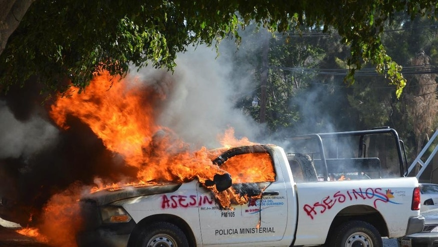 A police vehicle burns after teachers marching to demand justice for the 43 missing students, attacked the State Attorney General's offices in the state capital city of Chilpancingo, Mexico, Monday Dec. 1, 2014. According to Mexican officials, the students were detained by local police on Sept 26 in the city of Iguala, who apparently turned them over to a drug gang that reportedly killed them and incinerated their bodies but relatives remain skeptical of the government's version of the students fate. (AP Photo/Alejandrino Gonzalez)